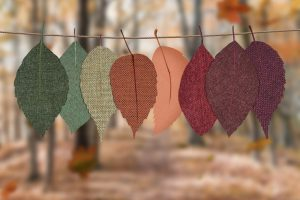 Fabric leaves hanging from a line going from a green leaf to a dark red leaf