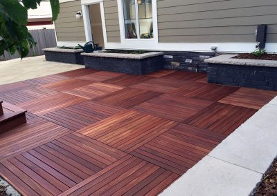 outside deck living area with a beautiful wooden tiled deck landscaped by Ananda Landscapes