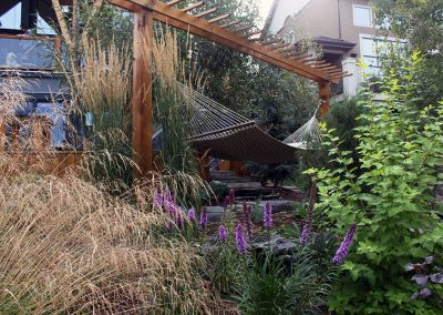 Hammock in the middle of a beautiful landscaped backyard by Ananda Landscapes in Calgary