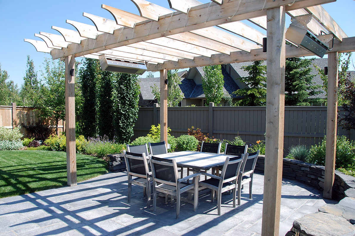 Landscaping Calgary Pergola overtop an outdoor dining table built by Ananda Landscapes