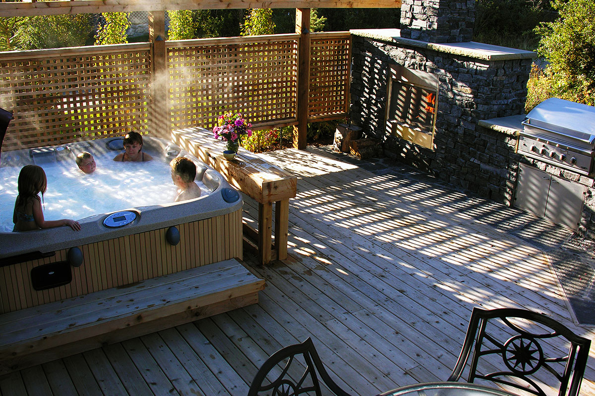 hot tub on a deck with privacy screen built in Calgary by Ananda Landscapes