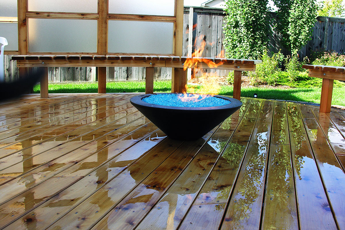 Outdoor fire bowl on a wooden deck built in Calgary by Ananda Landscapes