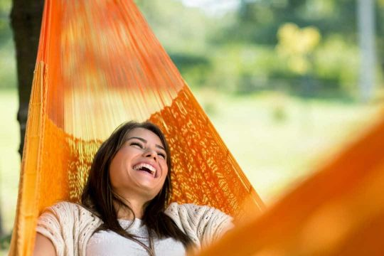Woman smiling in an outdoor hammock located in a backyard