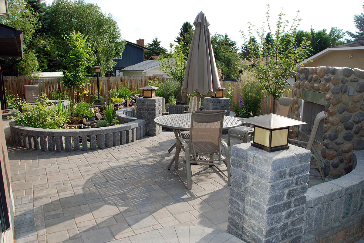 Outdoor backyard dining area with landscaped cobblestone deck detail