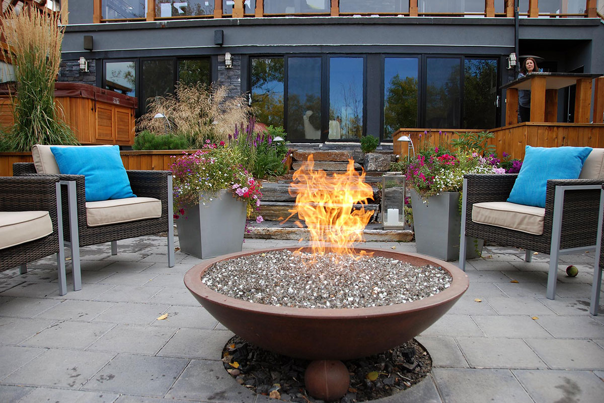 Outdoor fireplace in Calgary surrounded by patio chair on a tiled surface by Ananda Landscapes